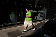 A large man admires himself as he walks past a polished clothing shop window in central London. Wearing a bright lime green t-shirt the obese male in shorts and trainers holds his stomach as he self-consciously walks past the reflective glass