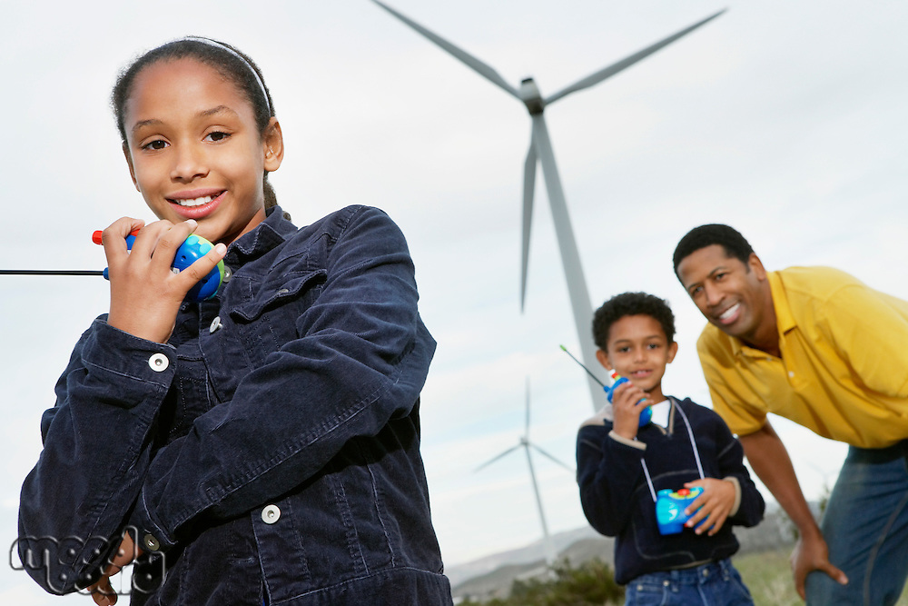 Father and children (7-9) playing with walky-talkies at wind farm