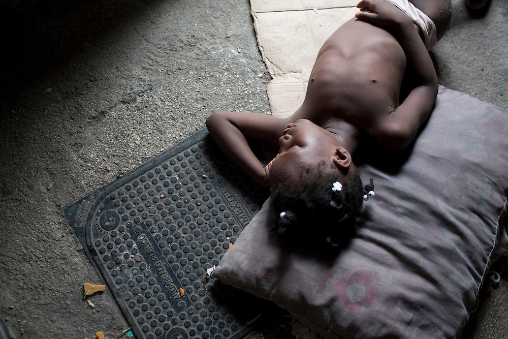 A girl sleeps on the ground inside a tent in a camp for people displaced by the earthquake on Champs de Mars on July 14, 2010 in Port-au-Prince, Haiti.