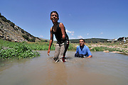 Israel, Negev, Two Beduin boys one with an amputated arm play in a water puddle