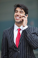 Happy Indian businessman communicating on cell phone
