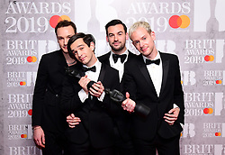Matthew Healy, Ross MacDonald, George Daniel and Adam Hann of The 1975 with their Best British Group and Mastercard British Album of the Year Brit Awards in the press room at the Brit Awards 2019 at the O2 Arena, London.