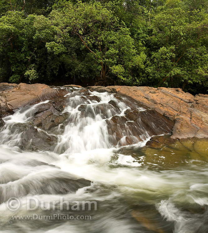 The Kuala Jasin waterfall where the Jasin River flows into the Endau River, in Endau-Rompin National Park, Malaysia. This humid jungle is one of the world's oldest rainforest.  It has survived, untouched by the ice ages, for 130 million years.