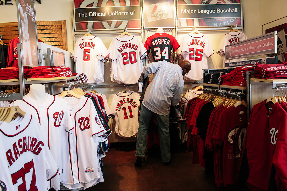 "Barry Walton, a Washington D.C. native, searches for Washington Nationals jerseys at the Nationals Clubhouse Team Store on Sept. 18, 2014. ""I get tired of seeing Orioles gear,"" Walton, who works at a Maryland-based company, said. ""I want to shove it down their necks."""