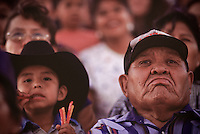 In the stands, a young spectator snacks on licorice during the Dilkon Buckaroo Days Rodeo. From spring through fall there is a rodeo somewhere on the Navajo Nation almost every weekend. The Navajo Nation, home to approximately 175,000 people, encompasses 25,000 square miles spanning the Arizona – New Mexico border and a sliver of southeastern Utah.