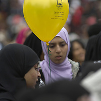 Young muslim women  wearing hijab holding Islamic Relief balloon at Eid in the Square, London, England<br />