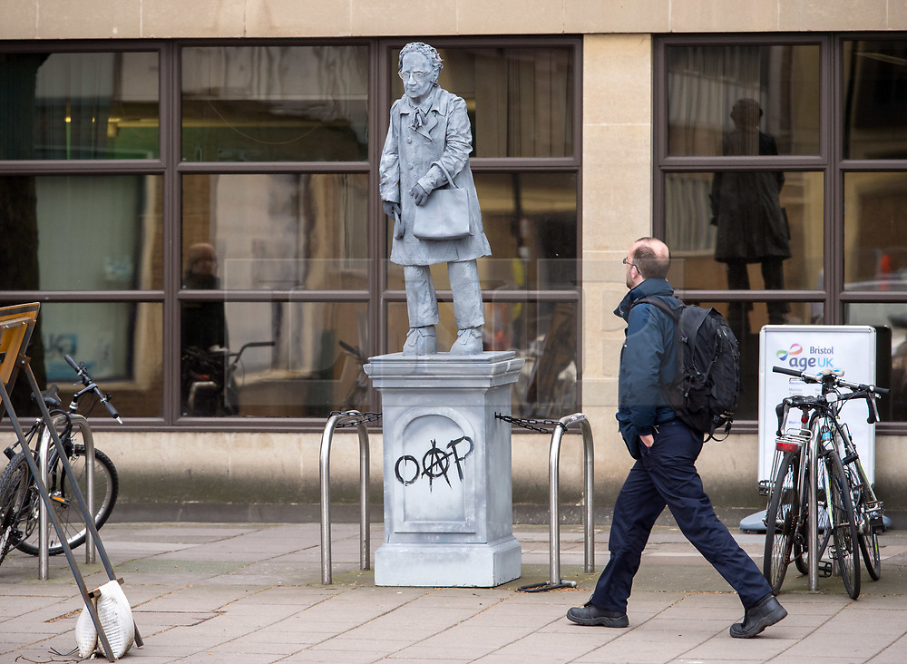 "© Licensed to London News Pictures. 24/04/2018. Bristol, UK. A statue of an elderly lady holding her handbag and a hammer has been put up on Victoria Street in Bristol city centre. The statue has ""OAP"" with the ""A"" as an anarchist symbol painted on the plinth, and has been chained to two bicycle stands outside the offices of Age UK. Staff working at Age UK Bristol found the 10-foot tall statue in front of their offices when they arrived at work on Monday, but know nothing about the statue. There have been unconfirmed reports the statue is a tribute to a lady by an anonymous artist, as the name ""Ruth"" is written on the back of the plinth.  Photo credit: Simon Chapman/LNP"