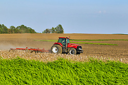 Farmer pulling an implement through a grain field in central Illinois