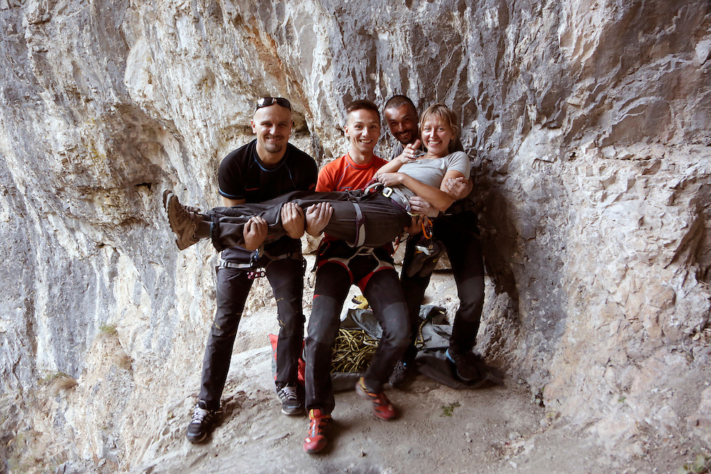 Besim Muminovic, Armin Gazic and Kenan Muftic holding the Via Dinarica photographer Elma Okic at the sports climbing area 'Pecine' near Bugojno, Bosnia and Herzegovina.