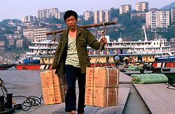 CHINA SICHUAN PROVINCE CHONGQUING MAY99 - A dockworker carries goods from a ferry at the shore of the Yangtse river where it merges with the Jailing river at Chongquing. Seven large cities, including Chongquing, and thousands of villages will be submerged once the water level rises after the completion of the controversial Three Gorges Dam project further downriver. The flooding of areas reaching back more than 550Km upriver will require the evacuation and resettlement of more than 10 million people.  jre/Photo by Jiri Rezac. © Jiri Rezac 1999. . Contact: +44 (0) 7050 110 417. Mobile:  +44 (0) 7801 337 683. Office:  +44 (0) 20 8968 9635. . Email:   jiri@jirirezac.com. Web:     www.jirirezac.com