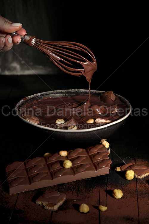 Woman hand with whisk mixing melted chocolate with peanuts in a bowl. <br /> This file is only available at Stockfood.com and can be purchased at this address: https://www.stockfood.it/fotografia-immagine/12468176/Woman-hand-with-whisk-mixing-melted-chocolate-with-peanuts-in-a-bowl?q=%5bType-image%5d%2f%5bPhotographer-f5319%5d%2f%5bSort-Date%5d&amp;i=5