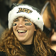 A fan wearing a Santa hat laughs prior to an NCAA football game between the South Florida Bulls and the 17th ranked University of Central Florida Knights at Bright House Networks Stadium on Friday, November 29, 2013 in Orlando, Florida. (AP Photo/Alex Menendez)