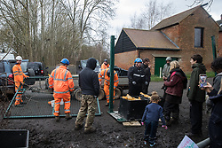 Harefield, UK. 13 January, 2020. Stop HS2 activists observe a team of construction engineers, accompanied by enforcement agents, erecting a gate across a public right of way leading to an activist protection camp. Activists were evicted by bailiffs from part of the nearby Colne Valley protection camp last week. 108 ancient woodlands are set to be destroyed by the high-speed rail link and further destruction of trees for HS2 in the Harvil Road area is believed to be imminent.