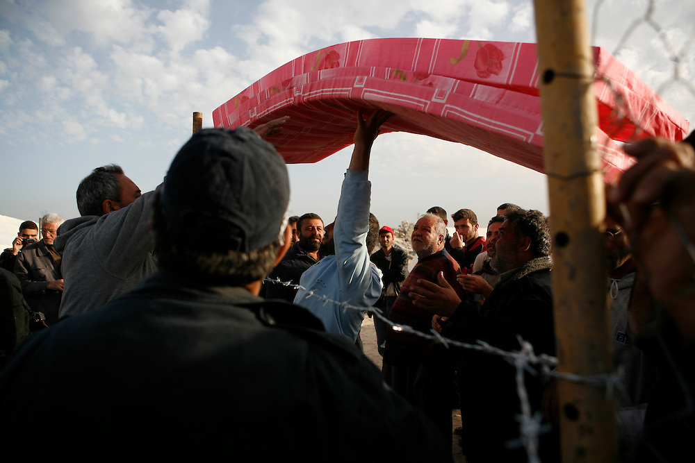Blankets and mattresses are handed out to Palestinians whose homes were destroyed in Israeli attacks in the Gaza Strip.