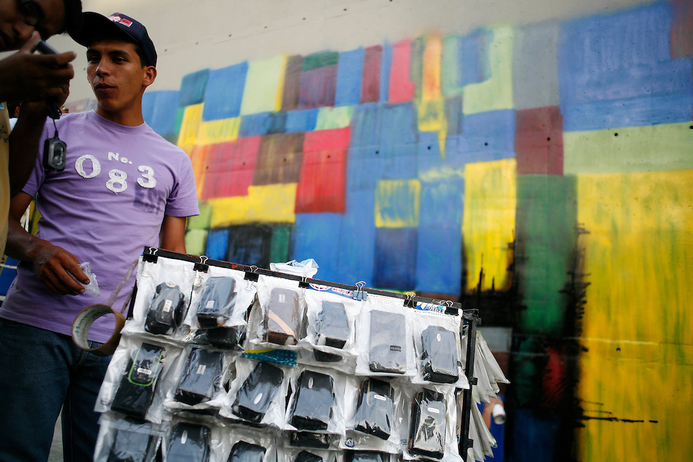 A young man sells cell phone accessories to graffiti artists commissioned by the government to replicate famous paintings on the walls outside the National Art Museum just prior to the museum's grand opening.