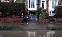© Licensed to London News Pictures. 29/12/15<br /> York, UK. <br /> <br /> A woman jogs along a path now visible as flood water begins to subside on Huntington Road in York. Further rainfall is expected over coming days as Storm Frank approaches the east coast of the country.<br /> <br /> Photo credit : Ian Forsyth/LNP