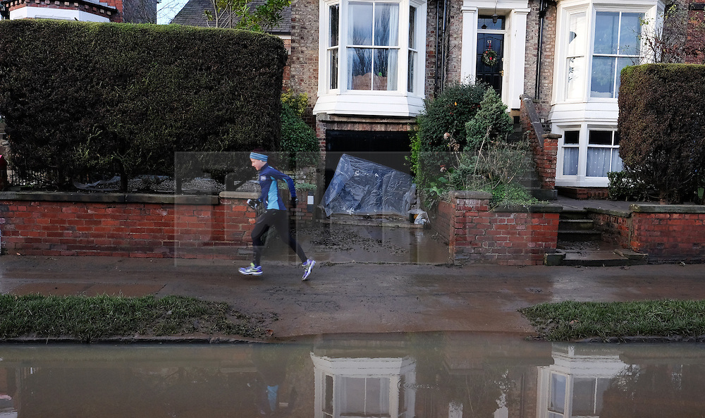 &copy; Licensed to London News Pictures. 29/12/15<br /> York, UK. <br /> <br /> A woman jogs along a path now visible as flood water begins to subside on Huntington Road in York. Further rainfall is expected over coming days as Storm Frank approaches the east coast of the country.<br /> <br /> Photo credit : Ian Forsyth/LNP