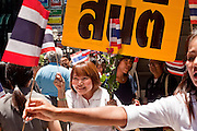 Apr. 19 2010 - BANGKOK, THAILAND: Women hand out Thai flags to passers before an anti-Red Shirt rally in the Silom financial district of Bangkok Monday. Hundreds of Thai soldiers, including reservists and front line units, and riot police moved into the Silom financial district Monday, not far from the red-shirts' main protest rally site, in Ratchaprasong. The heavy show of force is to prevent the Red Shirts from entering the Silom area. Many of soldiers were greeted as heros by workers in the area, who oppose the Red Shirts.   Photo by Jack Kurtz
