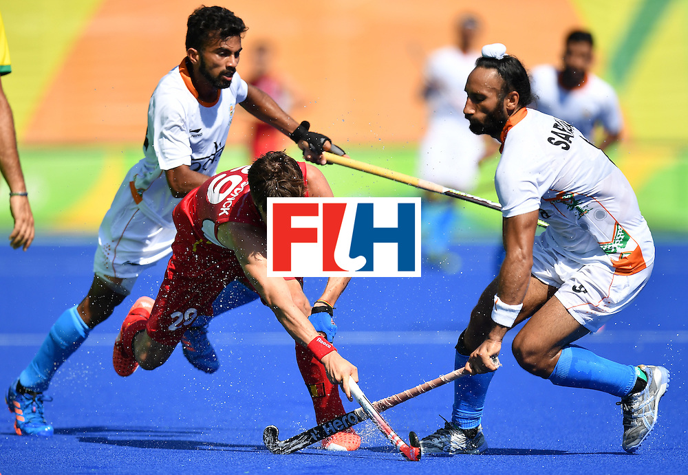 Belgium's Elliot van Strydonck (C) vies with India's Chandanda Thimmaiah (L) and India's Sardar Singh during the men's quarterfinal field hockey Belgium vs India match of the Rio 2016 Olympics Games at the Olympic Hockey Centre in Rio de Janeiro on August 14, 2016. / AFP / MANAN VATSYAYANA        (Photo credit should read MANAN VATSYAYANA/AFP/Getty Images)