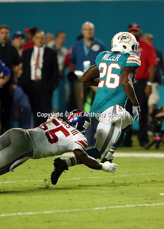 Miami Dolphins running back Lamar Miller (26) breaks free from a diving, shoestring tackle attempt by New York Giants outside linebacker J.T. Thomas (55) as he runs for a first quarter touchdown good for a 7-3 Dolphins lead during the NFL week 14 regular season football game against the New York Giants on Monday, Dec. 14, 2015 in Miami Gardens, Fla. The Giants won the game 31-24. (©Paul Anthony Spinelli)