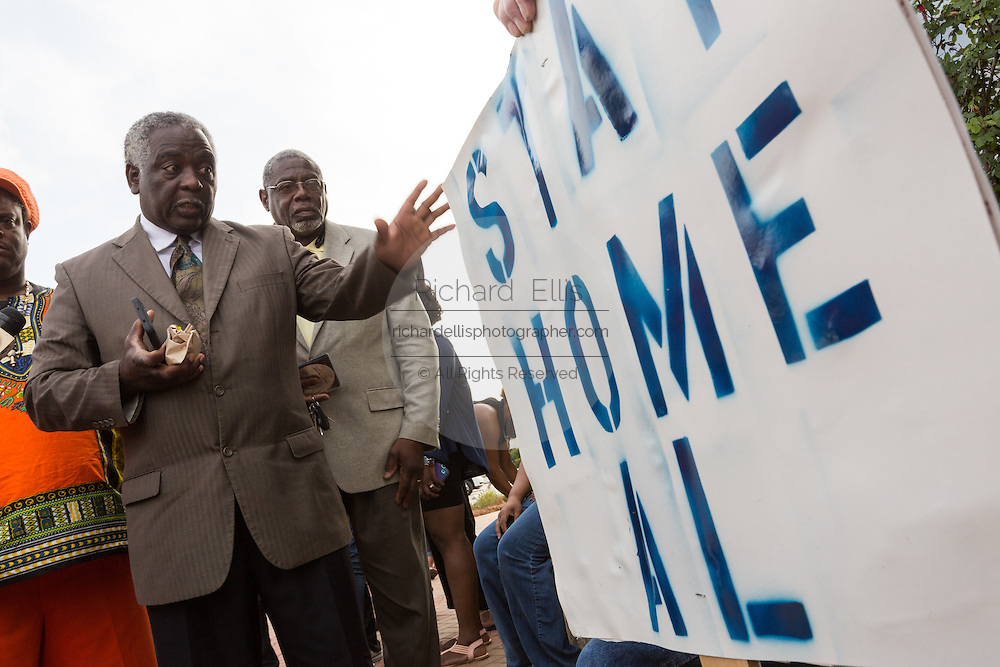 A local leader argues with a man holding a sign opposing the planned visit of Reverend Al Sharpton outside the North Charleston City Hall during a rally following the shooting death of Walter Scott April 10, 2015 in Charleston, South Carolina. Scott was shot multiple times by police after running from a traffic stop.