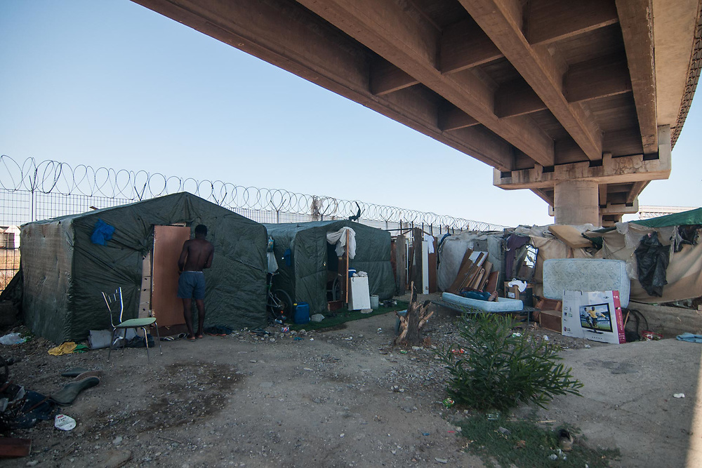 Illegal migrants enter to their tents in a camp near the railway station on August 03, 2017 in Crotone, Italy. The city of Crotone hosts one of the biggest european centre for migrants, but some of them live in clandestinity, even for two years, in an area near the city railway station, because they are afraid to be rejected and to be sent to their nations again. ©Simone Padovani
