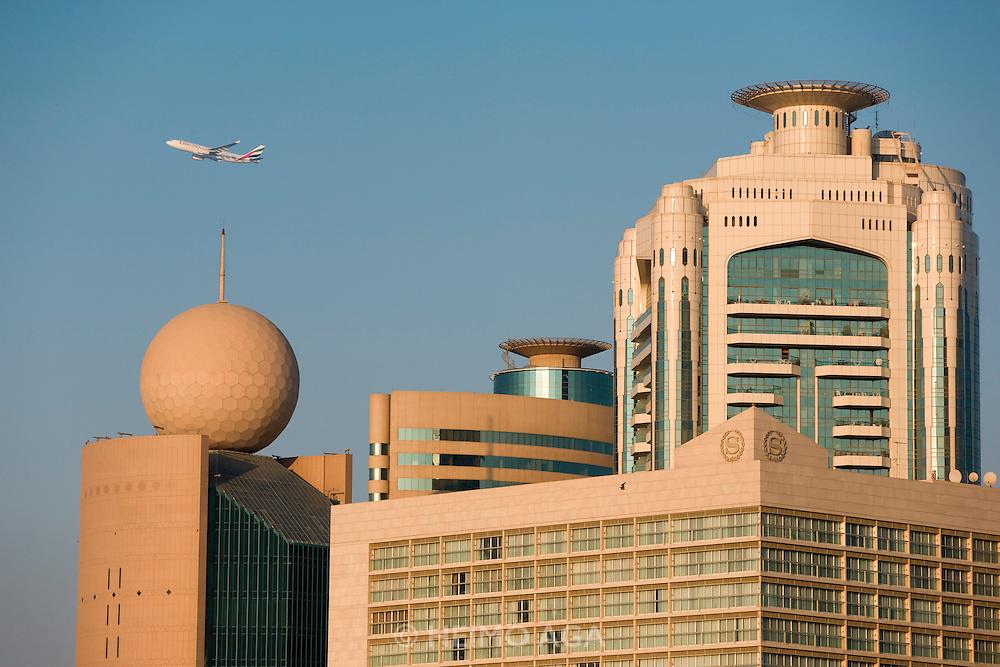 Dubai Creek. Deira skyline. Sheraton Dubai Creek (large cube foregr.), Etisalat Tower (l., with sphere on top). Emirates Airbus A330 starting from Dubai International Airport.