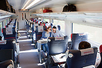 Florence, Italy - 28 April, 2012: A young couple travels in the first class of the Milan bound ITALO, Europe's first private operator of high-speed, domestic trains in Italy, in Florence, Italy, on April 28, 2012. The company's president is Ferrari chairman Luca Cordero di Montezemolo, one of the shareholders along with other private entrepreneurs like luxury businessmen Diego Della Valle, the French railway company, Italy's largest retail bank and the country's largest insurer. Italy's NTV (Nuovo Trasporto Viaggiatori) is the first company in Europe to compete with the state-run Trenitalia on high-speed service. When at full regime at the end of the year, 25 innovative trains will connect nine Italian cities, from Salerno to Milan, from Turin to Venice at 300km per hour. Italo passengers will board on stable trains that do not rely on a locomotive car, but has engines underneath each of the 11 carriages to increase capacity as well as safety.<br /> <br /> Ph. Gianni Cipriano for The New York Times