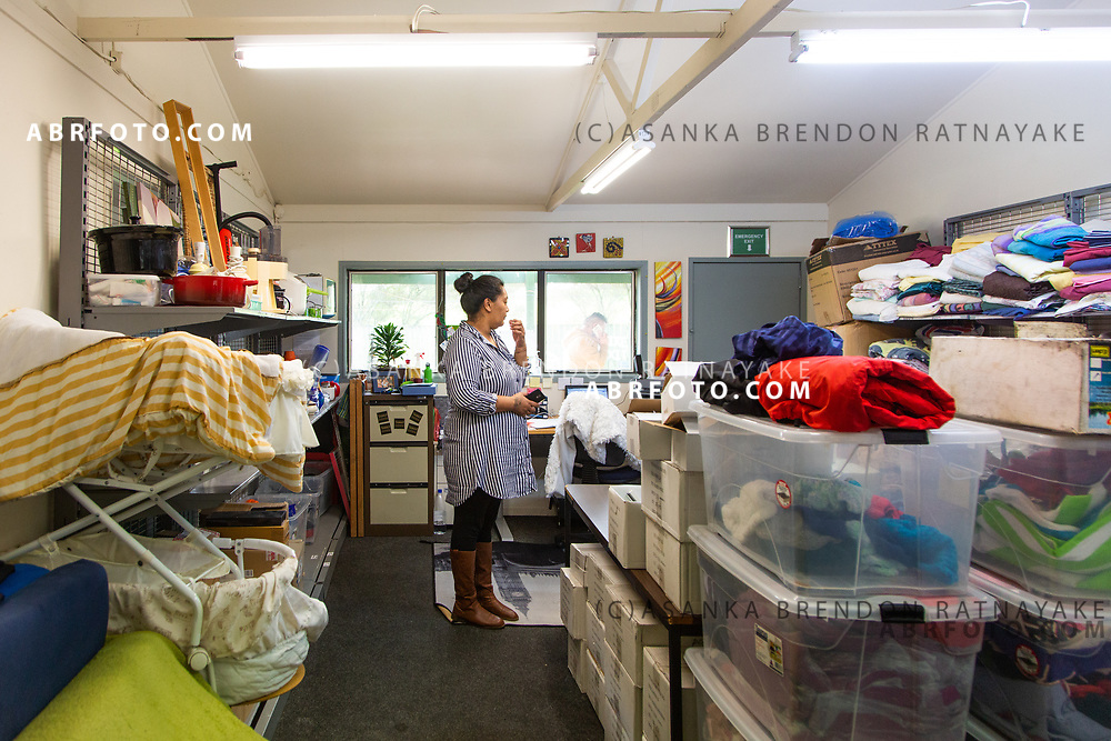 "Martha ""Moko"" Ewe at the Te Puea Marae sorts through housing items which were donated for homeless on the 5th of June 2018. Asanka Brendon Ratnayake for The New York Times."