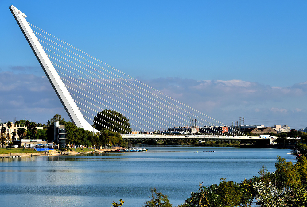 Puente del Alamillo Connecting Cartuja Island in Seville, Spain<br /> Puente del Alamillo is an elegant, cable-stayed bridge by Santiago Calatrava, a gifted Spanish architect known for his elegant designs. The 820 foot span over a canal of the Guadalquivir River was commissioned for the 1992 Universal Exposition. Alamillo Bridge connects to the Island of the Carthusians where Expo &rsquo;92 hosted over 42 million visitors during the six-month event.