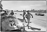 Sebring 12-Hour race • March 21, 1964 • Hill throws a piece of broken wind wing towards pit wall   •  Shelby Cobra roadster #14 Ford V8 289 (5-liter) GT5.0 • finished 6th co-driver Jo Schlesser  •  Jim Culleton at rear of car  •  Ferrari 275P in background (finished 2nd)