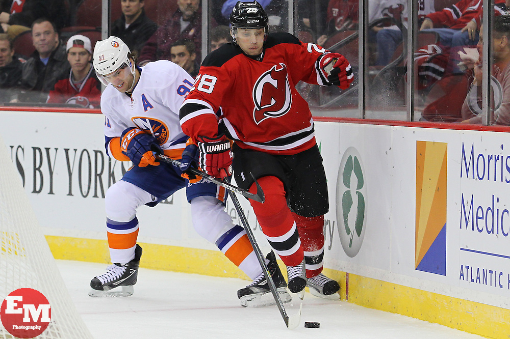 Jan 31, 2013; Newark, NJ, USA; New Jersey Devils defenseman Anton Volchenkov (28) battles for the puck with New York Islanders center John Tavares (91) during the first period at the Prudential Center.