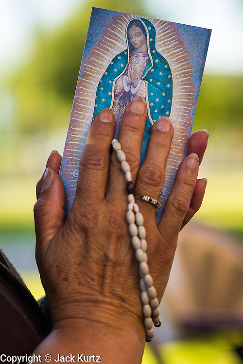 18 JUNE 2012 - PHOENIX, AZ:  A woman holds a Virgin of Guadalupe prayer card during a vigil against SB 1070 Monday. About 20 people, members of the immigrant rights' group Promise AZ (PAZ) held a prayer vigil at the Arizona State Capitol in Phoenix Monday praying that the US Supreme Court would overturn SB 1070, Arizona's controversial anti-immigrant law. The court's ruling had been expected Monday, June 18 but the the court said the ruling would not come out until later this month. Members of PAZ said they would continue their vigil until the ruling was issued.    PHOTO BY JACK KURTZ