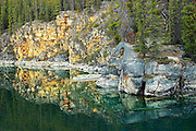 SHoreline rocks reflected into Horseshoe Lake<br /> Jasper National Park<br /> Alberta<br /> Canada