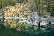 SHoreline rocks reflected into Horseshoe Lake<br /> Jasper National Park<br /> Alberta<br /> Canada