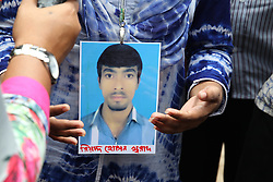 September 12, 2016 - Tongi,Dhaka, Bangladesh - Sathi hold his brother photos who work in a Tampaco factory still his brother missing. A team of Bangladesh Army  and  firefighter jointly  at work the Tampaco factory  on 12 September, 2016 at tongi near Dhaka, Bangladesh. The rescuers have recovered four more bodies from the spot, as the death toll rises to 33. A huge fire has broken out at the five-storey factory building of Tampaco Foils Ltd after a boiler exploded around 6am on Saturday. Photo: Monirul Alam (Credit Image: © Monirul Alam via ZUMA Wire)