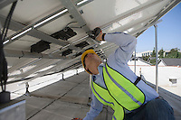 Maintenance worker adjusting solar panel in Los Angeles California