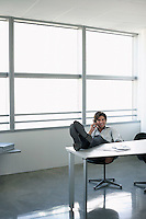 Business man using mobile phone sitting at office desk with feet up