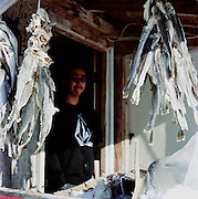 "Justin Eningowok outside of his home in Shishmaref, Alaska in March 2010. Tomcods, a small white fish caught in the spring and enjoyed frozen, swing from the Eningowok's porch throughout the year. ""The liver is the delicacy,"" Justin told us, ""and my grandmother said the belly skin is for sickness."""