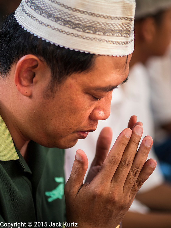 17 JULY 2015 - BANGKOK, THAILAND:     A man prays during Eid services at Ton Son Mosque in Bangkok. Eid al-Fitr is also called Feast of Breaking the Fast, the Sugar Feast, Bayram (Bajram), the Sweet Festival or Hari Raya Puasa and the Lesser Eid. It is an important Muslim religious holiday that marks the end of Ramadan, the Islamic holy month of fasting. Muslims are not allowed to fast on Eid. The holiday celebrates the conclusion of the 29 or 30 days of dawn-to-sunset fasting Muslims do during the month of Ramadan. Islam is the second largest religion in Thailand. Government sources say about 5% of Thais are Muslim, many in the Muslim community say the number is closer to 10%.          PHOTO BY JACK KURTZ