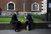 Two businessmen eat takeaway lunches in St Botolph-without-Bishopsgate churchyard