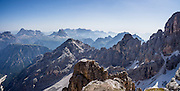 "From Rifugio Guido Lorenzi on Monte Cristallo in the Ampezzo Dolomites, look northeast across blue ridges of the Sesto Dolomites (Dolomiti di Sesto, or Sexten/Sextner/Sextener Dolomiten) towards the pyramids of Tre Cime di Lavaredo (Italian for ""Three Peaks of Lavaredo,"" called Drei Zinnen or ""Three Merlons"" in German). A lift to Forcella Staunies on Monte Cristallo gives unforgettable views over the Dolomites mountains (part of the Southern Limestone Alps) near Cortina d'Ampezzo, in the Province of Belluno, Veneto region, Italy, Europe. Monte Cristallo lies within Parco Naturale delle Dolomiti d'Ampezzo. Directions: From Cortina, drive 6km east on SR48 to the large parking lot for Ski Area Faloria Cristallo Mietres (just west of Passo Tre Croci Federavecchia). Take a chair-lift from Rio Gere to Son Forca (rising from 1698m to 2215m). Then take the old style ovovia (egg-shaped) Gondellift Forcella Staunies to Rifugio Guido Lorenzi (2932m) for astounding views. Climbers enjoy spectacular via ferrata routes here. Cortina gained worldwide fame after hosting the 1956 Winter Olympics. UNESCO honored the Dolomites as a natural World Heritage Site in 2009. This panorama was stitched from 2 overlapping photos."