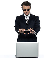 one criminal man computer hacker  caucasian computing on the phone  in studio isolated on white background