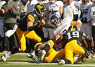 October 26 2013: Northwestern Wildcats quarterback Kain Colter (2) is taken down by Iowa Hawkeyes defensive back Tanner Miller (5), Iowa Hawkeyes defensive lineman Drew Ott (95), and Iowa Hawkeyes defensive back B.J. Lowery (19) during the third quarter of the NCAA football game between the Northwestern Wildcats and the Iowa Hawkeyes at Kinnick Stadium in Iowa City, Iowa on October 26, 2013. Iowa defeated Northwestern 17-10 in overtime.