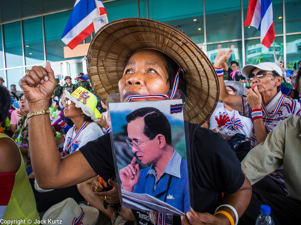 "08 APRIL 2014 - BANGKOK, THAILAND:  A Thai anti-government protestor holds up a picture of Bhumibol Adulyadej, the King of Thailand, while she blocks the entrance to the Ministry of Justice. Several hundred anti-government protestors led by Suthep Thaugsuban went to the Ministry of Justice in Bangkok Tuesday. Suthep and the protestors met with representatives of the Ministry of Justice and expressed their belief that Thai politics need to be reformed and that corruption needed to be ""seriously tackled."" The protestors returned to their main protest site in Lumpini Park in central Bangkok after the meeting.   PHOTO BY JACK KURTZ"
