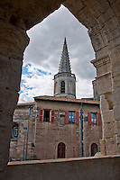 Church tower and house with red shutters seen through a Coliseum arch in the old town of Arles, France.