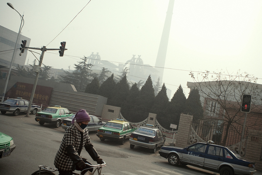 A woman with a bike passes by the main electric factory of Lanzhou, Guo Jian, which uses cial a s energy source and is one of the main source of pollution of the town. China.<br /> <br /> -------<br /> Lanzhou, in the Gansu province is the most polluted cities of China and in the world's top ten for atmospheric pollution due to human activity. The town is situated between two hills along the Yellow River and the polluted clouds remain blocked over the town. The sky is most of the time hidden by the pollution.