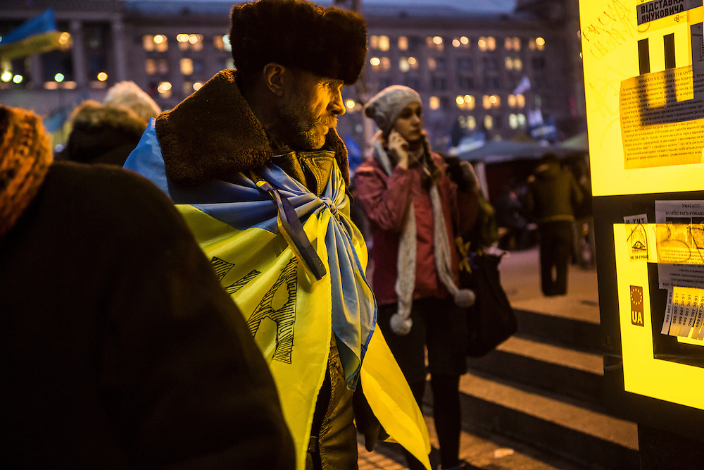 KIEV, UKRAINE - DECEMBER 5: A man read a poster on Independence Square on December 5, 2013 in Kiev, Ukraine. Thousands of people have been protesting against the government since a decision by Ukrainian president Viktor Yanukovych to suspend a trade and partnership agreement with the European Union in favor of incentives from Russia. (Photo by Brendan Hoffman/Getty Images) *** Local Caption ***