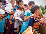"07 AUGUST 2014 - BANGKOK, THAILAND:  Children line up for free toys during a food distribution at Pek Leng Keng Mangkorn Khiew Shrine in Bangkok. Thousands of people lined up for food distribution at the Pek Leng Keng Mangkorn Khiew Shrine in the Khlong Toei section of Bangkok Thursday. Khlong Toei is one of the poorest sections of Bangkok. The seventh month of the Chinese Lunar calendar is called ""Ghost Month"" during which ghosts and spirits, including those of the deceased ancestors, come out from the lower realm. It is common for Chinese people to make merit during the month by burning ""hell money"" and presenting food to the ghosts. At Chinese temples in Thailand, it is also customary to give food to the poorer people in the community.<br />      PHOTO BY JACK KURTZ"