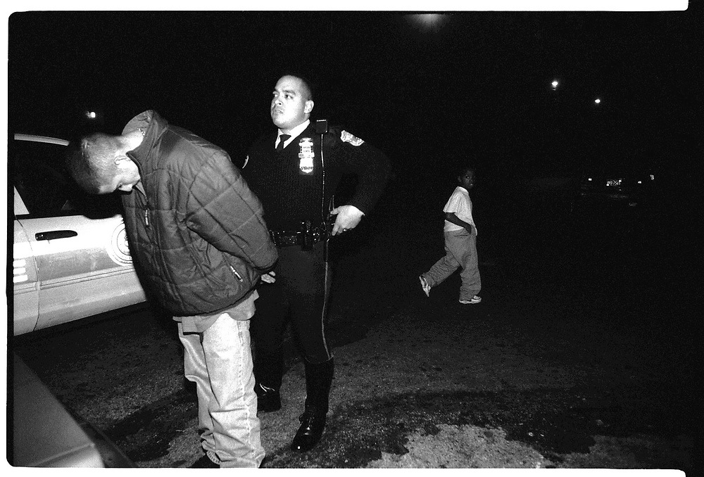 A kid watches as a man is arrested on the street.